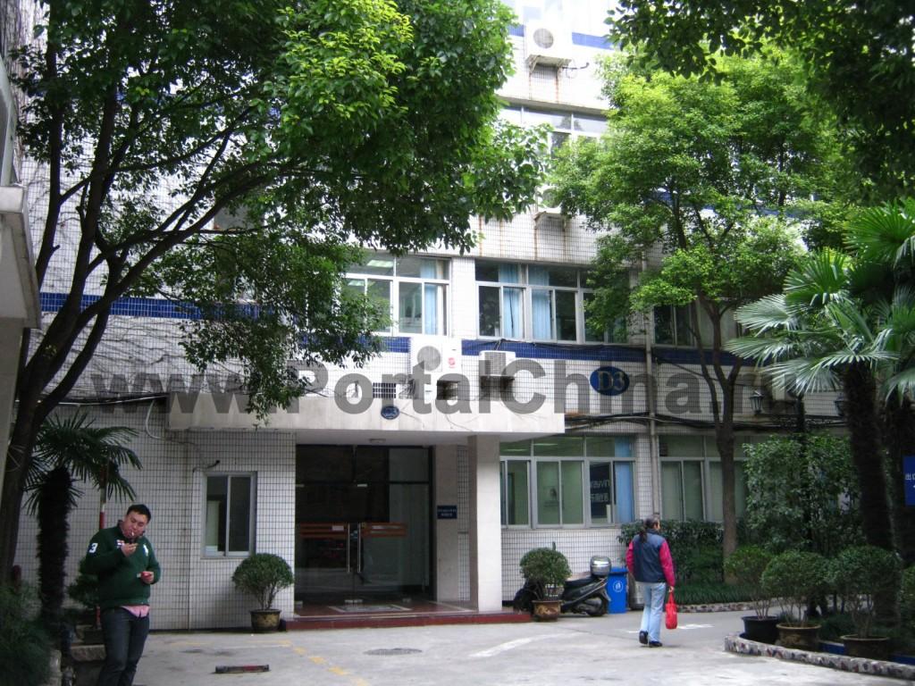 Shanghai Jiao Tong University – Chinese Language Centre, вход в здание белого цвета, окружен деревьями и кустарниками